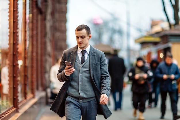 Молодой человек в пальто, прогуливаясь по улице и с помощью мобильного телефона