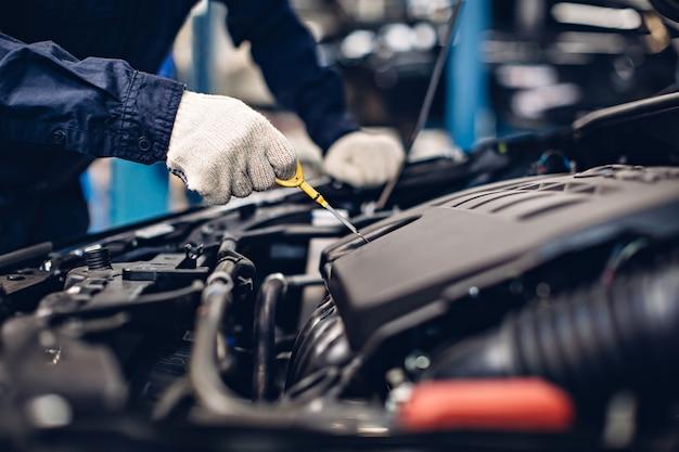 Механик проверяет уровень масла в двигателе