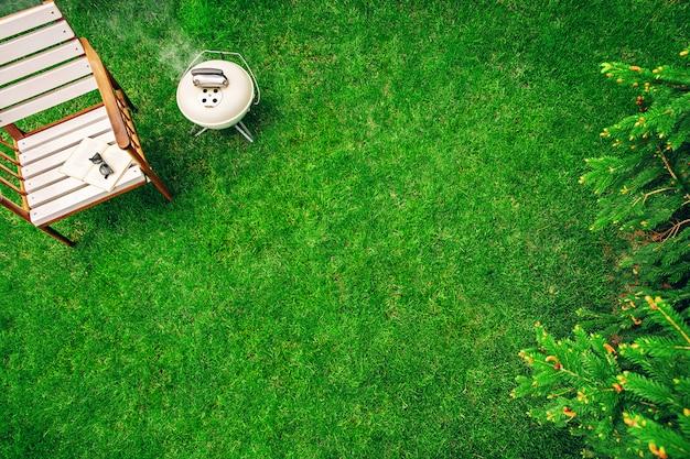 本とメガネで木製の肘掛け椅子の近くの芝生の上のアイボリー色のグリル。