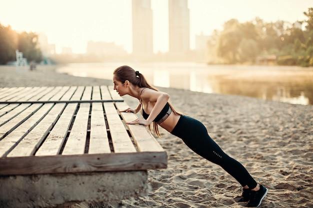 Девушка делает отжимания на деревянной платформе на берегу реки