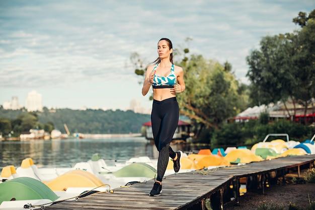ヨーロッパの女の子は川の海岸の木製の道を走る