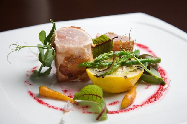 Свежий тунец с зеленой спаржей, блюдо для гурманов в ресторане. сочетание цвета и вкуса.