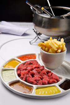 Мясное фондю с разными соусами и картофелем фри.