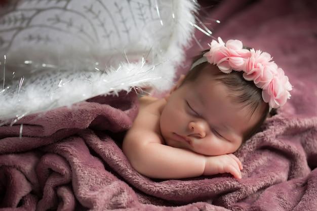 Портрет красивой новорожденного ребенка с крыльями ангела на фиолетовом одеяле