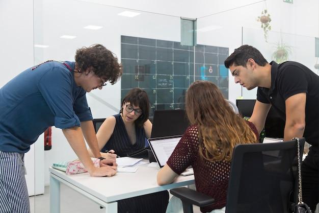 Молодые люди собрались в коворкинге, обсуждая новую маркетинговую кампанию.