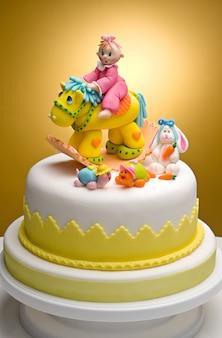 非常にカラフルなフォンダンで作られたキャラクターで、新生児用のケーキ