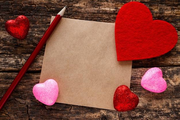 バレンタインの日心鉛筆とメモ木製の背景のモックアップ
