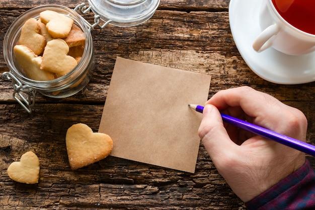 自家製クッキー、マグカップ、男はメモを書く