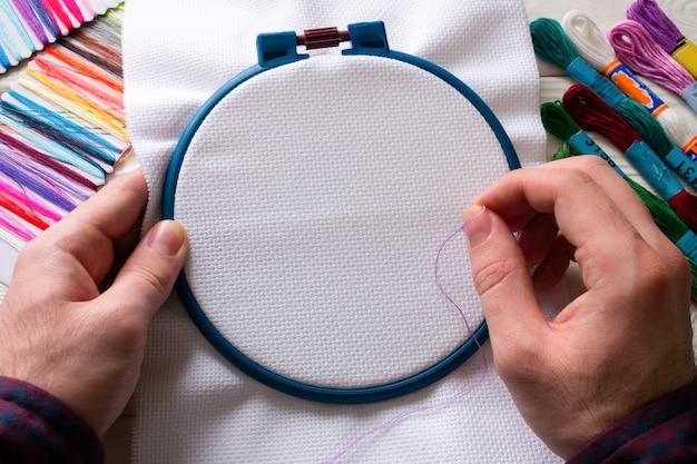 Человек вышивает цветной нитью