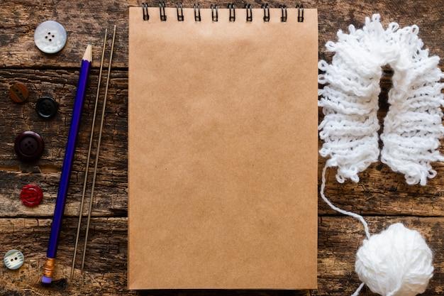 メモ帳の近くで縫う糸、鉛筆、編み針、糸