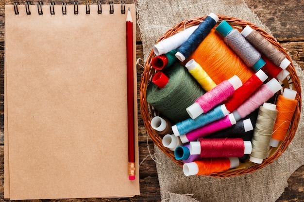 ノートと縫製用の色の糸付きバスケット