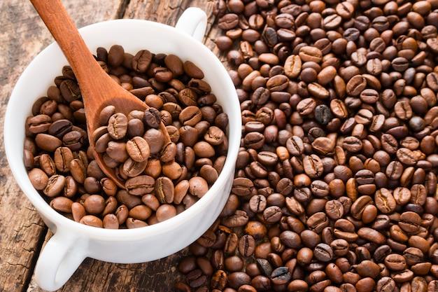 木のスプーンで白いカップでコーヒー豆のテーブル
