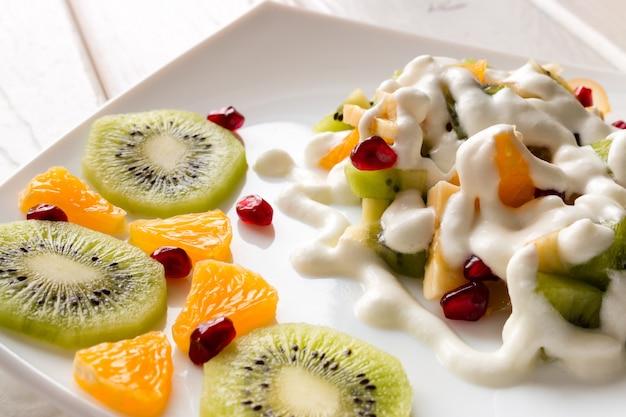 スライスしたフルーツの横にあるアイスクリームの白いプレートとフルーツサラダ