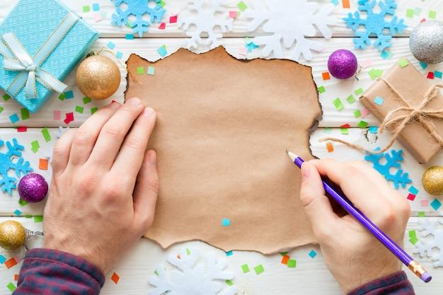 男は、クリスマスのおもちゃやギフトの希望をリストに書いています