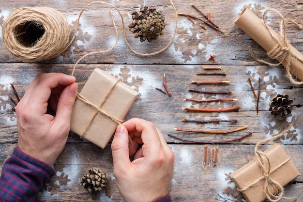 Мужчина оборачивает рождественские подарки деревянными