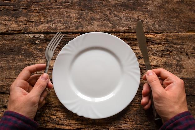 Мужчина держит нож и вилку рядом с тарелкой на деревянном