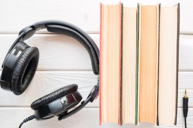 白い木製の背景上の古い本の横にあるヘッドフォン