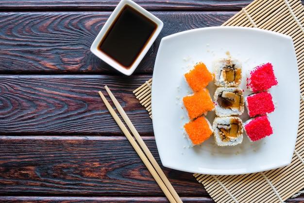 Суши роллы на белой тарелке и соевый соус на деревянном фоне