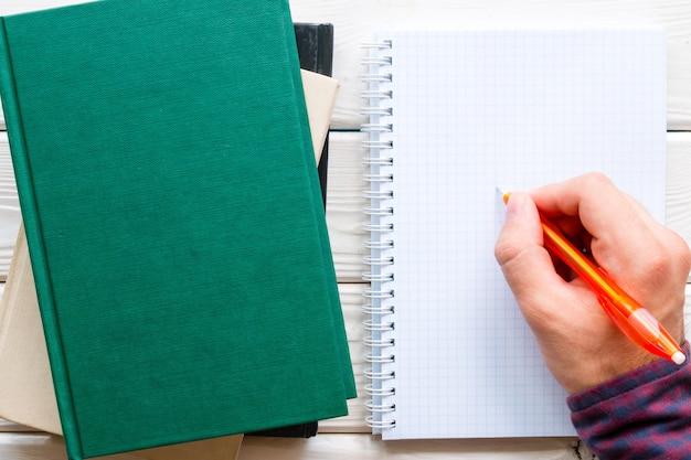 宿題をして、本のスタックの横にあるノートに書く学生