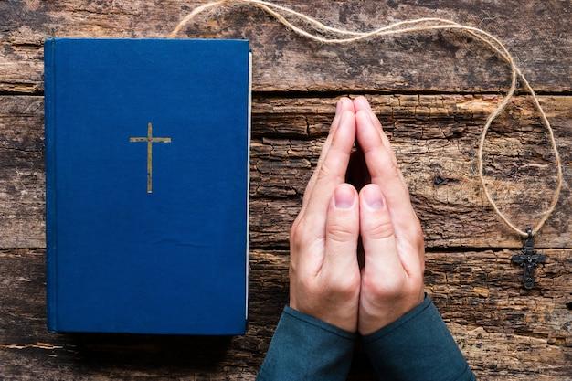 聖書の横に祈って、木製の背景にクロスする男