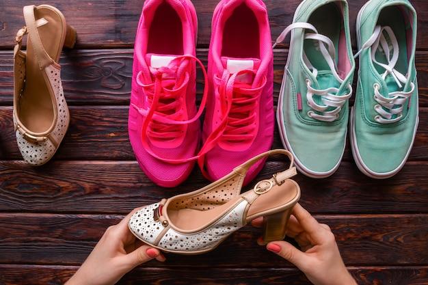 Девушка выбирает между женской обувью и кроссовками