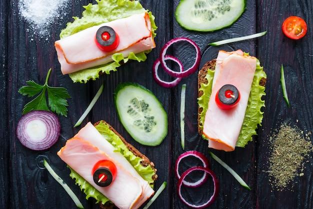 Бутерброды с мясом на листьях салата с овощами на черном