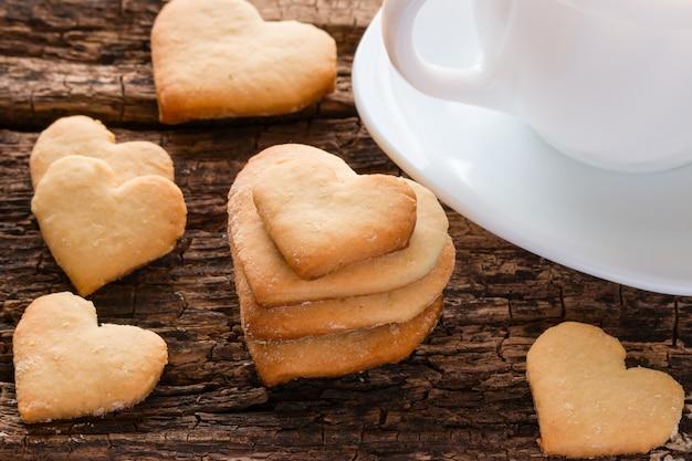Домашнее печенье в форме сердца и белая чашка деревянная