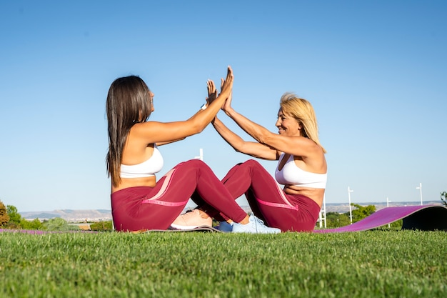 母と娘のカップルは屋外の公園でフィットネス運動トレーニングをして、勝利で自分の手のひらを衝突愛情と幸せな態度でスポーツをしています