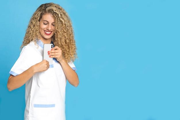 Женщина-врач со светлыми волосами держит свой мобильный телефон в белом халате