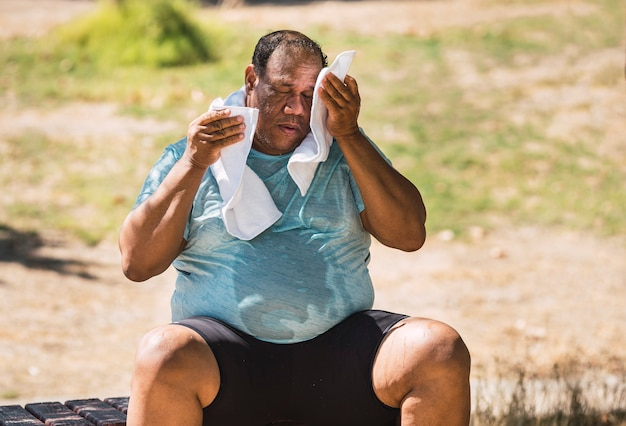 Пожилой темнокожий мужчина с ожирением и толстым сидит и сушит пот
