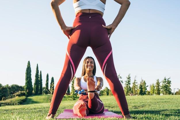 スポーツウェアに身を包んだパーソナルスポーツおよびフィットネストレーナーが屋外で年上の金髪の女性を訓練し、教師が輪ゴムでストレッチを行い、運動中に彼女の笑顔を幸せに見せます