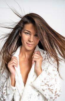 移動髪と白いレースのシャツを浮かべてきれいな髪と美しいブルネットの女性のクローズアップの肖像画