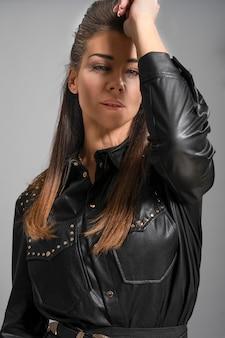 Портрет красивой женщины брюнетка с красивой улыбкой, одетые в одежду и кожаную куртку или меха в изолированных фоне