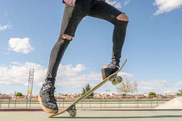 スケートパークでトリックを行うスケートボードを持つスケーター