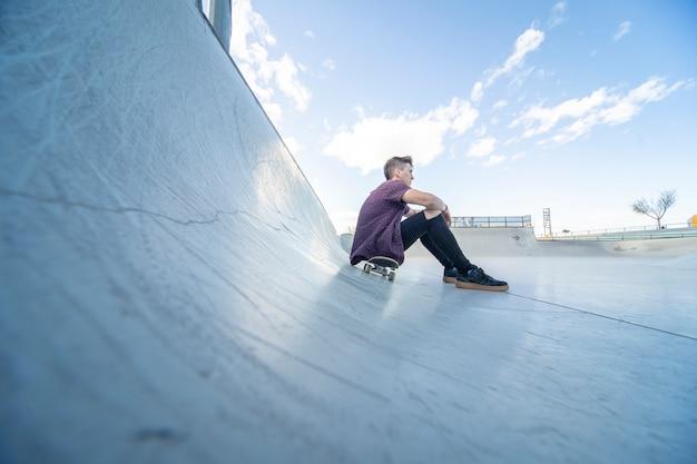 Конькобежец со скейтбордом в скейт-парке