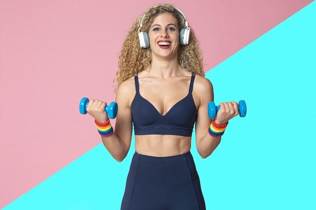Лесбиянка с фитнес-образом жизни занимается спортом, выполняет силовые тренировки, слушает музыку в наушниках