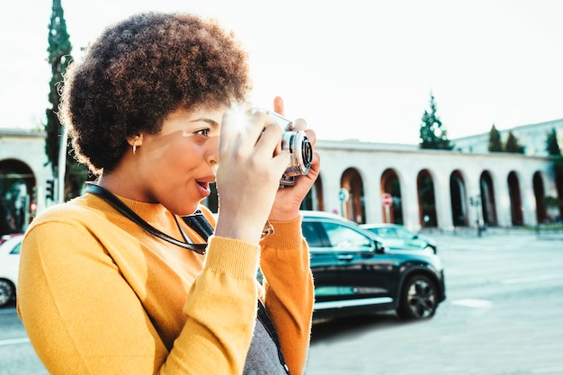 日没の観光で彼女のカメラで撮影美しい黒人女性