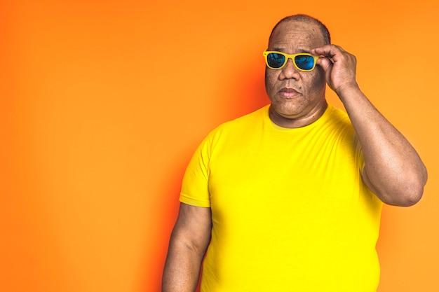 Старый черный человек с желтой рубашкой и солнцезащитными очками