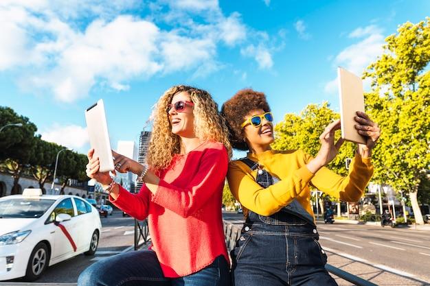 街の通りでスマートフォンを使用する友人。若者の電話とコミュニケーションの概念