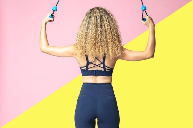 フィットネスライフスタイルの運動と運動とスリムな金髪女性の背面図
