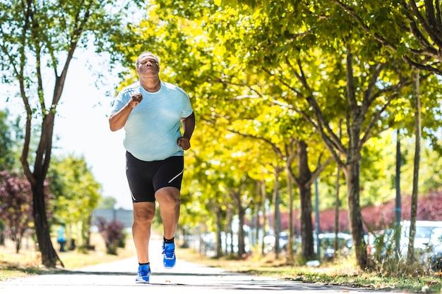 В парке бежит пожилой темнокожий мужчина, прилагая много усилий, чтобы уменьшить лишний вес