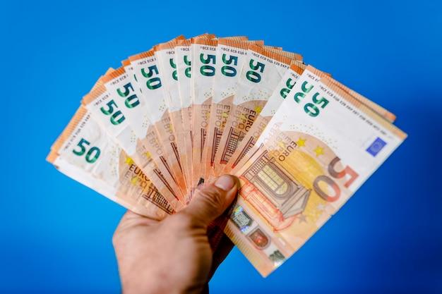 男の手は多くのユーロ紙幣を保持しています