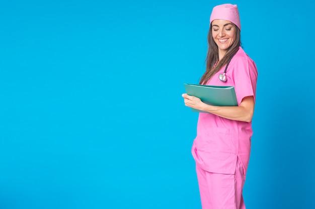 がんの子供の世話をするピンクのスカーフを持つ看護師