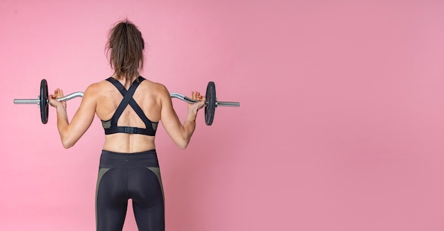 バーベルでウェイトトレーニングをしている女性の背面図