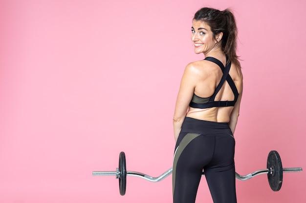 フィットネス女性トレーニングと笑顔の背面図