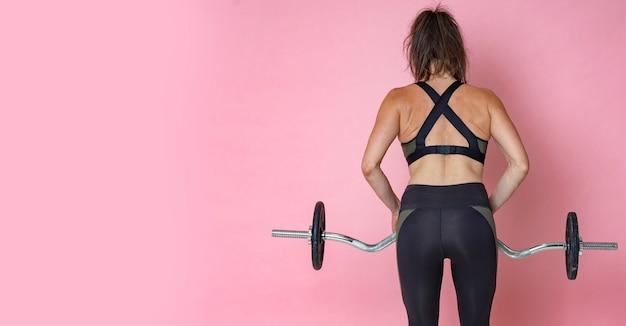 フィットネスライフスタイルトレーニングとダンベルバーベルでウェイトトレーニングを行う若い女性ブルネット