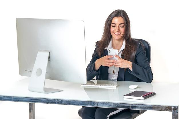 かなり若いエグゼクティブビジネスの女性とディレクターのオフィスに座って入力し、コンピューターの前にインターネット経由でクライアントとの会話を持つ彼女のスマートフォンとチャット