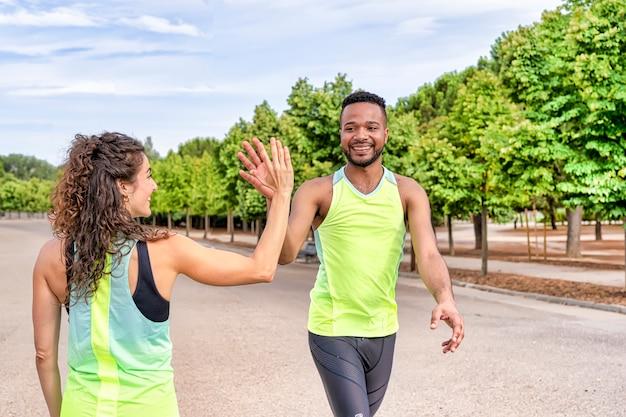 Пара чернокожего мужчины и белой женщины с удовольствием занимаются спортом и бегом, они приветствуют друг друга своими руками, они в парке одеты в спортивную одежду