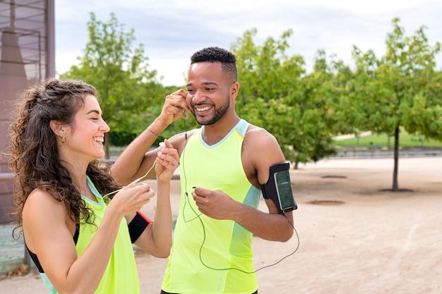 Пара счастливых и улыбчивых бегунов разной национальности, одетых в спортивную одежду, слушают музыку на своих смартфонах с наушниками