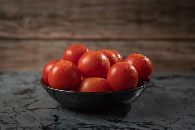 Большие красные помидоры на черной тарелке, на гранитном столе